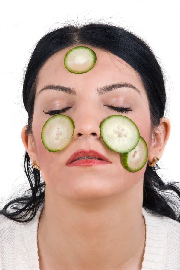 Van het het gezichtsmasker van de komkommer de jonge vrouw stock foto's