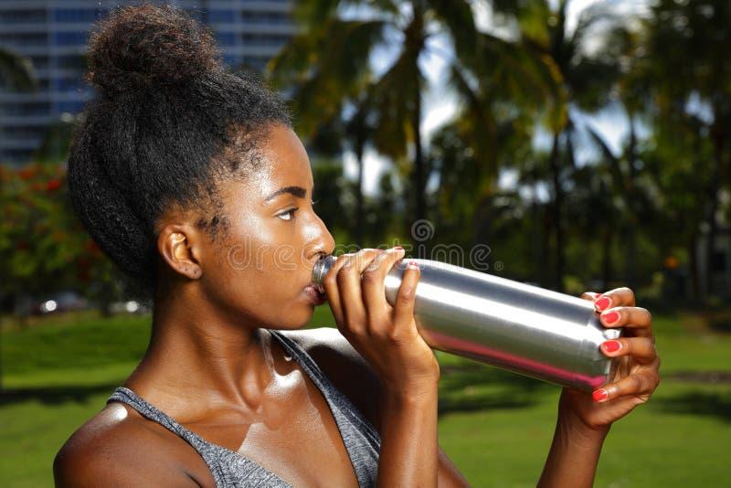 Van het het haarbroodje van het vrouwen drinkwater Afrikaanse Amerikaanse de flitsfoto in openlucht royalty-vrije stock foto's