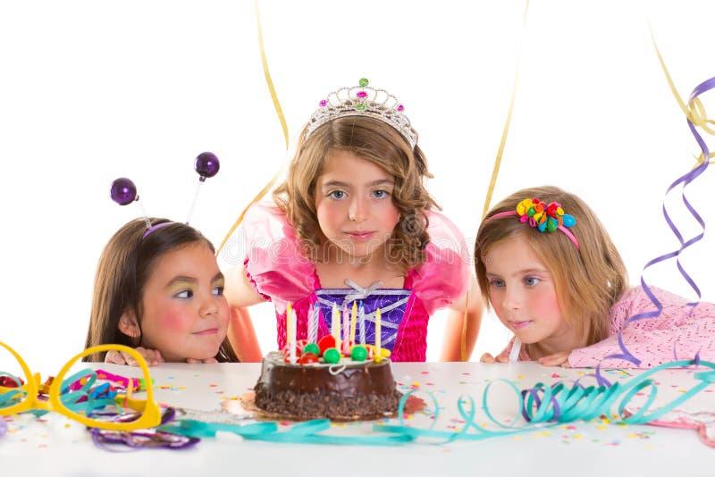 Van het jonge geitjemeisjes van kinderen de de verjaardagspartij kijkt opgewekte chocoladecake stock afbeelding