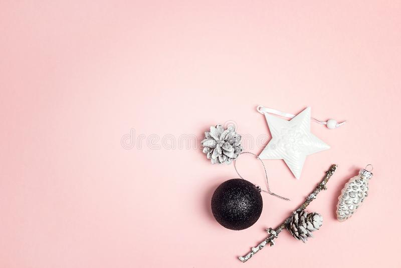 Van het Kerstmisdecoratie en exemplaar ruimte op een roze achtergrond Samenstelling van kegels, zwarte bal en witte ster royalty-vrije stock afbeelding