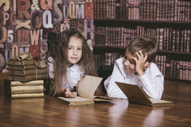 Van het kinderenjongen en meisje kinderen die boeken in bibliotheek lezen stock afbeelding
