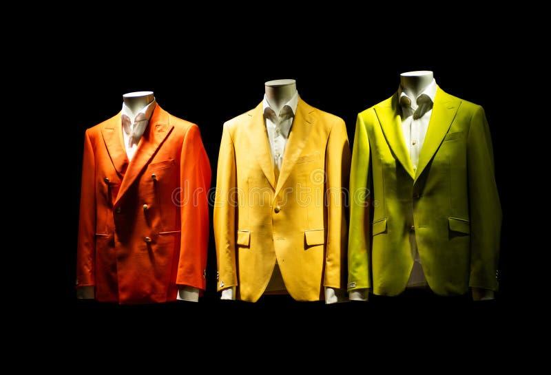 van het kostuumjasjes van 3 kleurrijke mensen oranje yello groen op vertoning stock afbeelding
