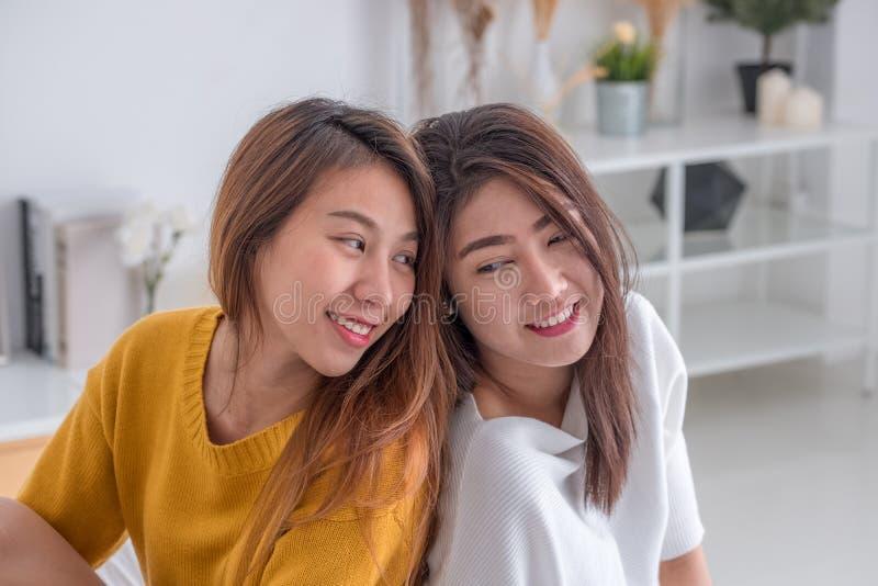 Van het lgbtpaar van Azië de de lesbische omhelzing en zitting op bed dichtbij witte windo stock foto's