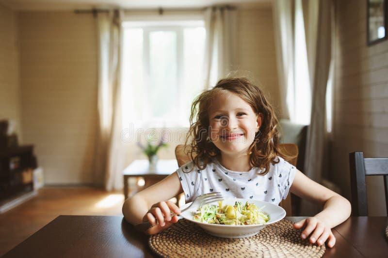 8 van het oude gelukkige kindjaar meisje die deegwaren thuis voor lunch eten royalty-vrije stock fotografie
