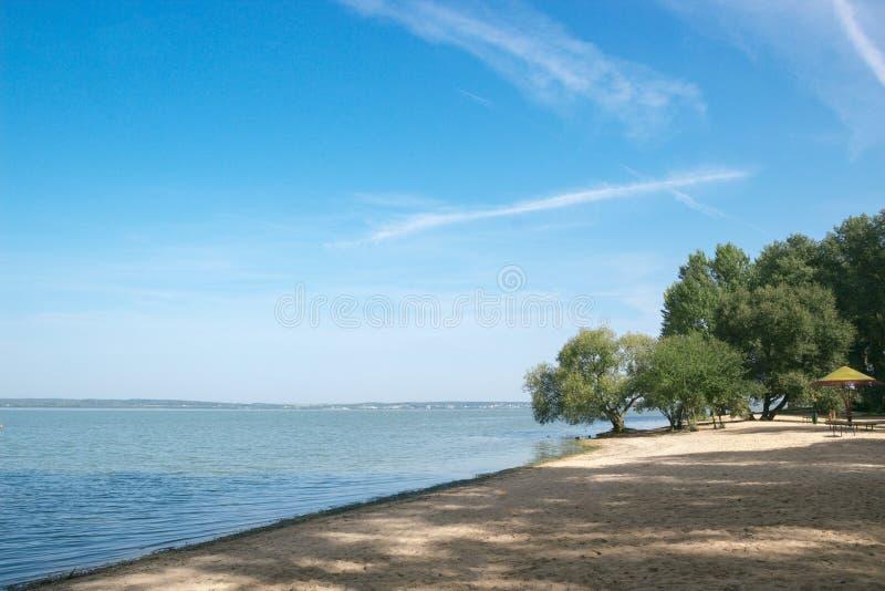 Van het overzeese van het de baai blauwe water zandstrand de hemelbomen op de kust royalty-vrije stock fotografie