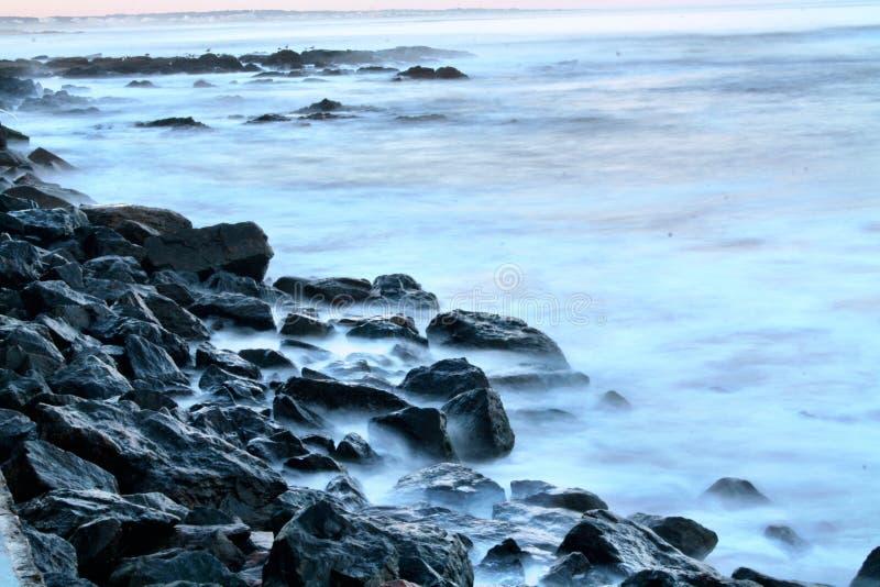 Van het overzeese van de strandzonsondergang de rotsen magisch uur zonsopgangwater stock foto