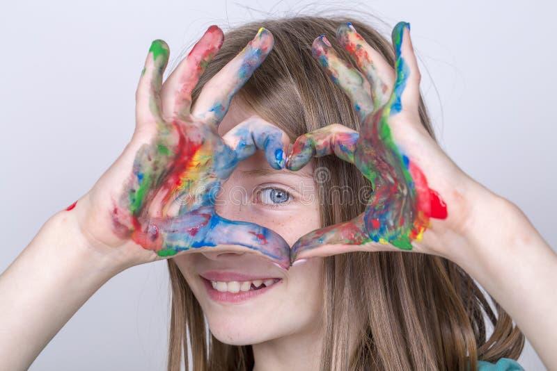 Van het portret maken de jonge meisje en kind geschilderde handen een hartvorm Schoolmeisjehanden die een kleurrijk hartsymbool v stock foto's