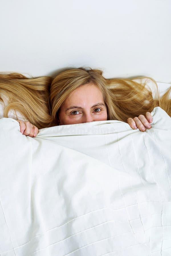 Van het het portretbed van de middenleeftijdsvrouw ziet echt van het de slaapkamerblonde lang haar vijftig plus exemplaar ruimte  royalty-vrije stock foto