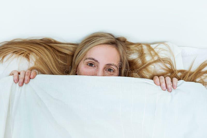 Van het het portretbed van de middenleeftijdsvrouw ziet echt van het de slaapkamerblonde lang haar vijftig plus exemplaar ruimte  stock foto's