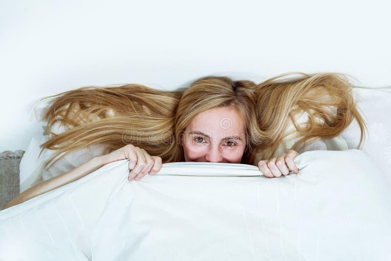 Van het het portretbed van de middenleeftijdsvrouw ziet echt van het de slaapkamerblonde lang haar vijftig plus exemplaar ruimte  stock foto