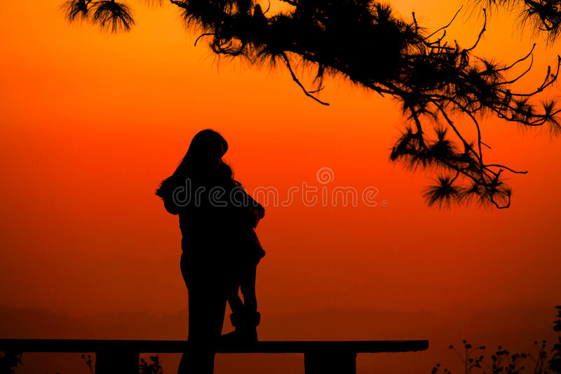 Van het silhouetmoeder en Kind minnaars natuurlijke achtergrond bij het strand en de berg stock foto's