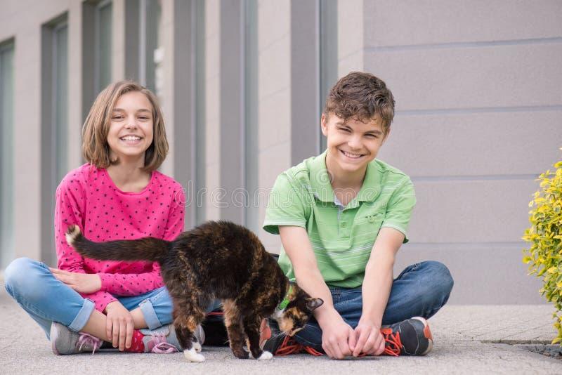 Van het tienerjongen en meisje het spelen met kat royalty-vrije stock afbeeldingen