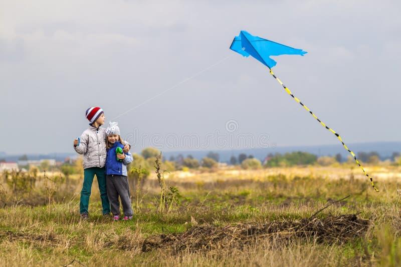 Van het twee het kleine kinderenjongen en meisje spelen buiten met een vlieger royalty-vrije stock afbeeldingen