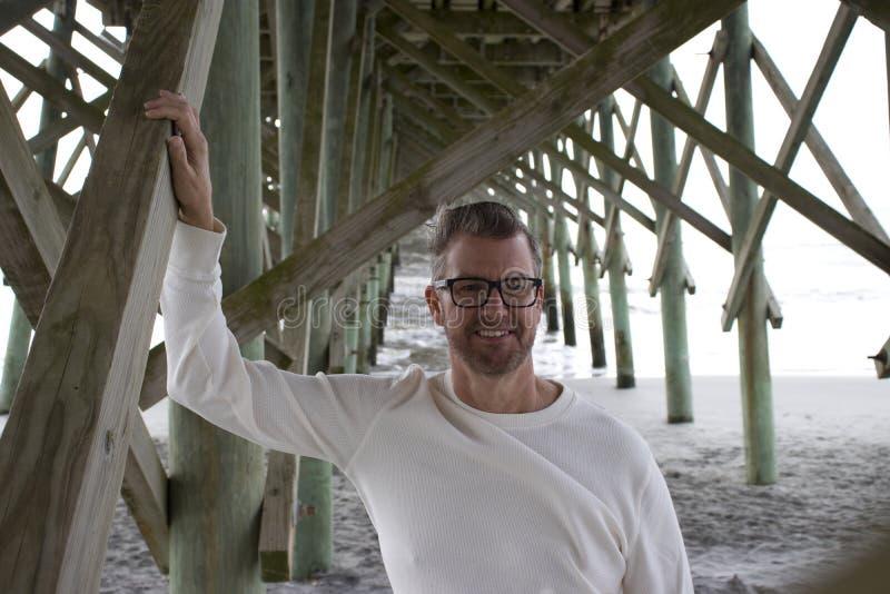 Van het Zuid- dwaasheidsstrand Carolina, 17 Februari, 2018 - de Mens longsleeved binnen wit overhemd die zich onder strandpijler  stock foto's