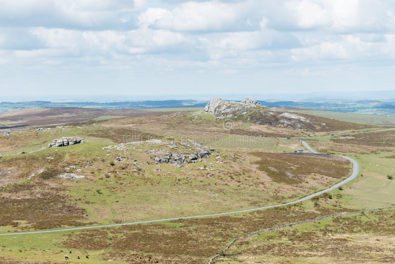 Van links naar rechts een mening van Emsworthy-Rotsen, Zadelpiek en Haytor over heide van het Nationale Park van Dartmoor, Devon, stock foto's