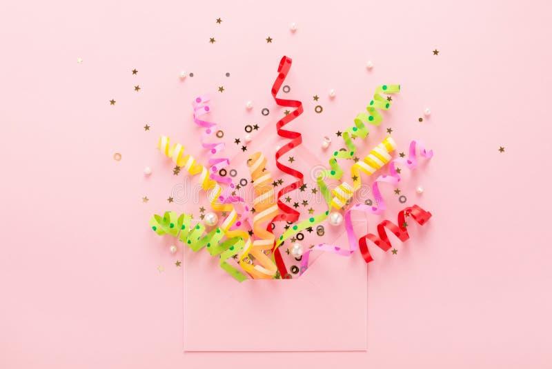 Van partijconfettien & lovertjes explosie van envelop op roze royalty-vrije stock fotografie