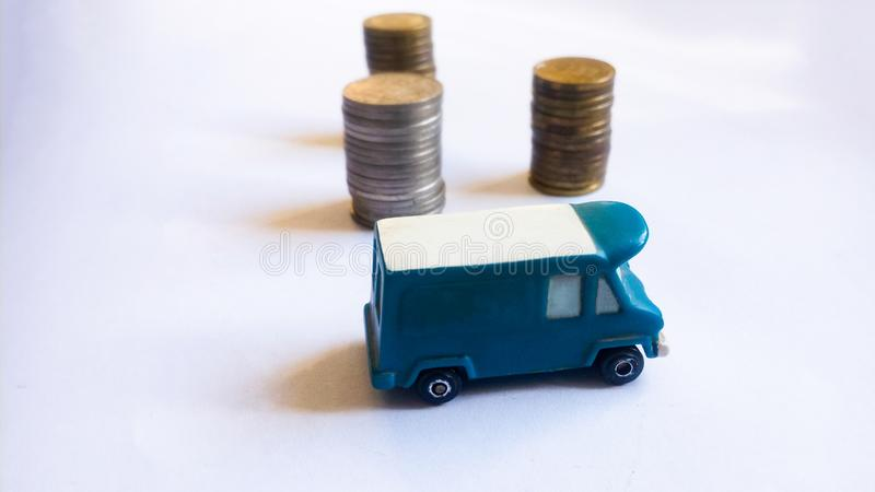 Van with Piled Coins. Toy van that is blue with coins stacked behind it and on white royalty free stock photo