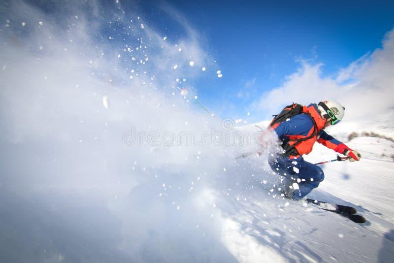Van piste die met skiër skien die op sneeuw met poedersleep berijden stock afbeeldingen