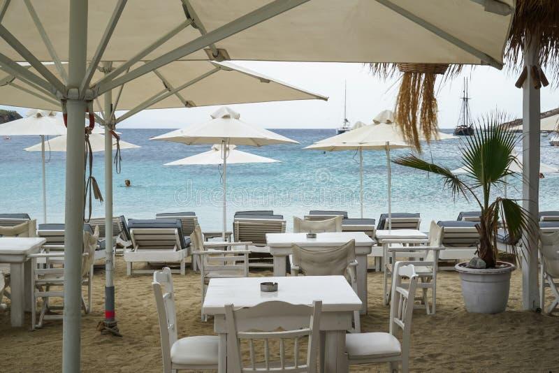 Van restaurantlijsten en stoelen de opstelling onder paraplu in witte kleur en lange stoel in blauw op Ornos schuurt strand met s stock foto