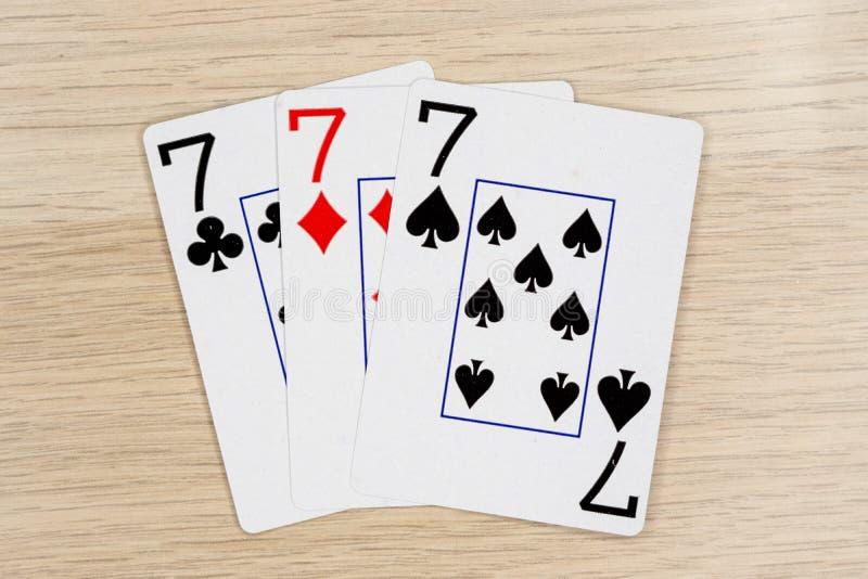 3 van vriendelijke sevens 7 - casino het spelen pookkaarten stock fotografie