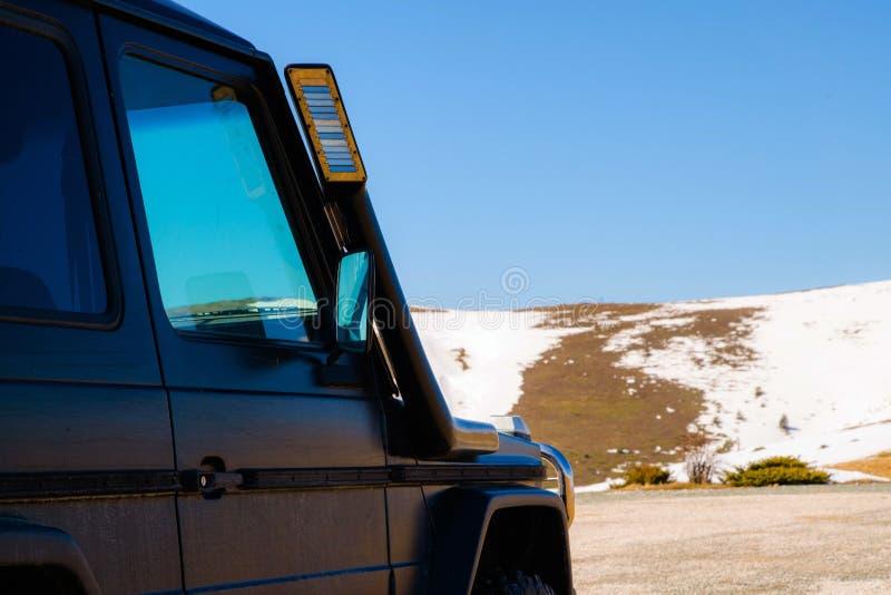 Van weg4x4 auto in de sneeuwbergen op een zonnige dag Het Off-road reizen, al terreinvoertuig in aard stock foto