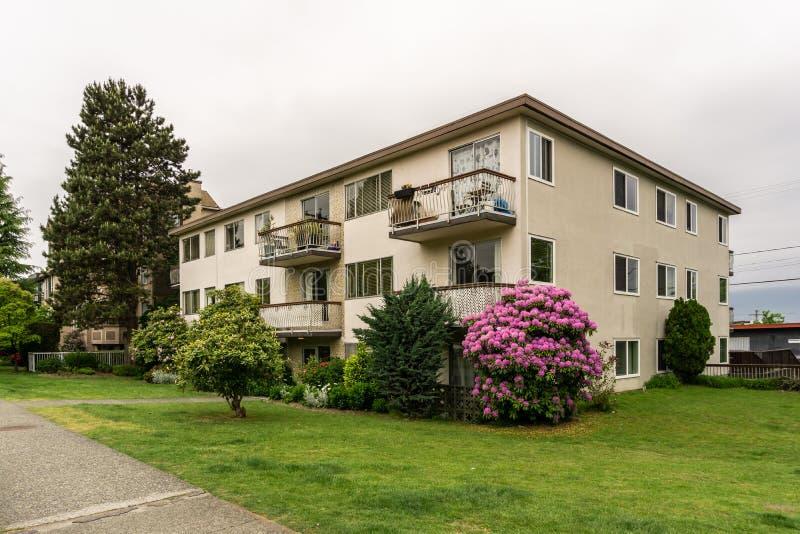 VANCÔVER, CANADÁ - 19 de maio de 2018: Casa residencial do Street View com o arbusto enorme com flores fotografia de stock