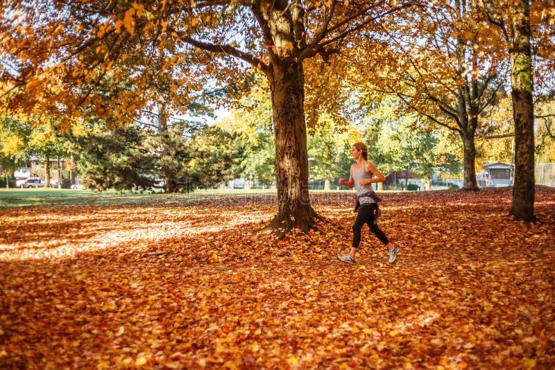 Vancôver Canadá - 29 de outubro de 2017 jovem mulher desportiva que corre no parque do amarelo do outono na manhã fotografia de stock royalty free