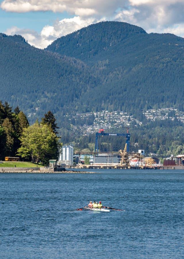 Vancôver, Columbia Britânica, - 5 de maio de 2019: Grupo brilhantemente vestido do enfileiramento do scull no porto de carvão fotografia de stock royalty free