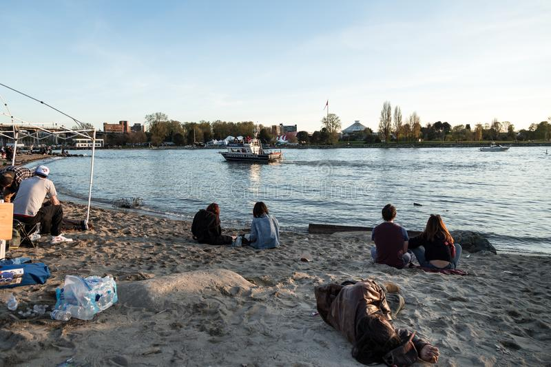 VANCOUVER, BC, CANADA - APR 20, 2019: A homeless man sleeping on the beach at the 420 festival in Vancouver. stock image