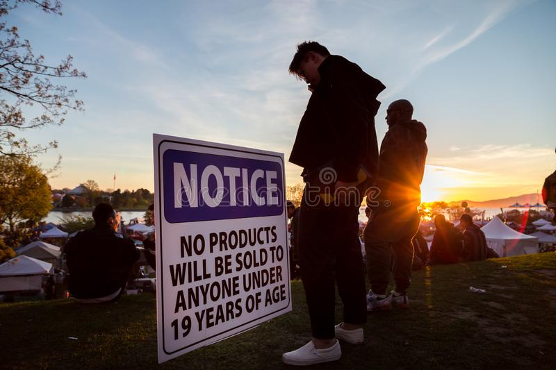 VANCOUVER, BC, CANADA - APR 20, 2019: A young man standing next to a vendor age restriction sign at the 420 festival in stock images
