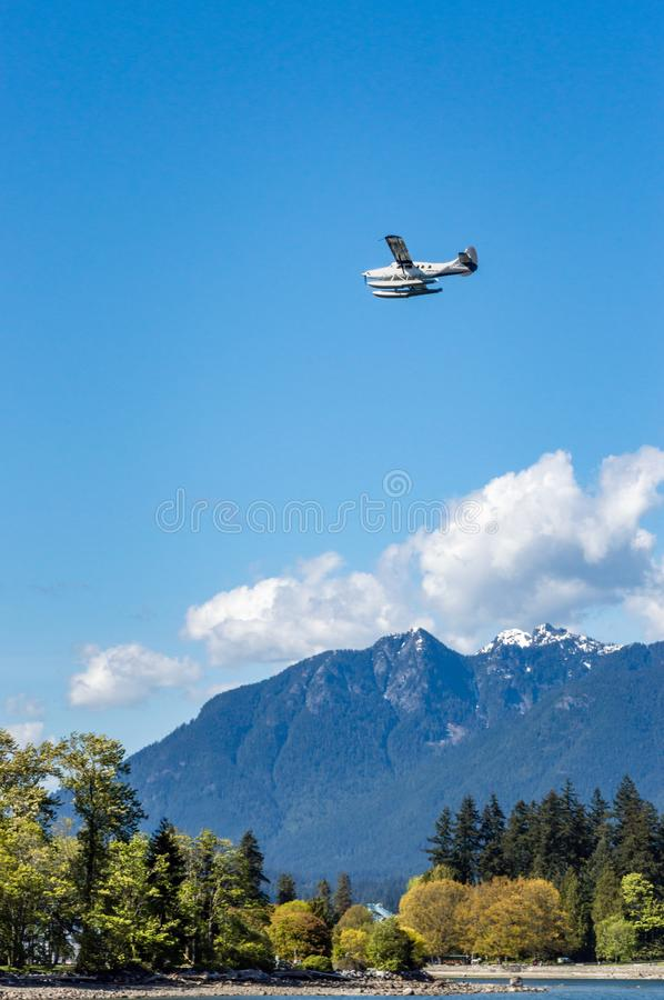 Vancouver, British Columbia, - May 5, 2019:  Fairmont Hotel commuter plane flying West over Coal Harbour. stock image