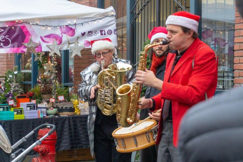 Vancouver, A.C., Canadá - 11/25/18: Músicos de jazz que tocan el saxofón, el tambor, y la trompeta en Yaletown CandyTown incluso  fotografía de archivo libre de regalías