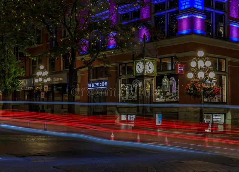 Traffic light trails by the steam-powered clock in Gastown, national historic site in Vancouver, Canada after sunset royalty free stock photo
