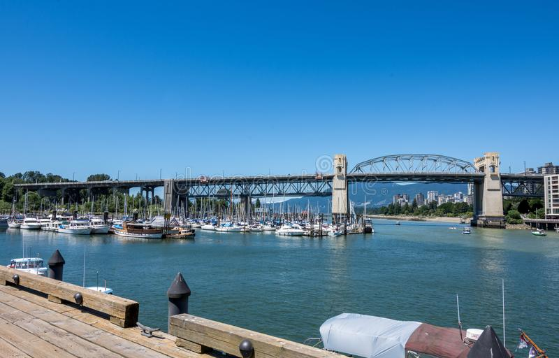 Vancouver, Canada - June 23, 2017: Boats in the Burrard Civic Ma. Rina with Vancouver`s downtown in the background as seen from Granville island stock image
