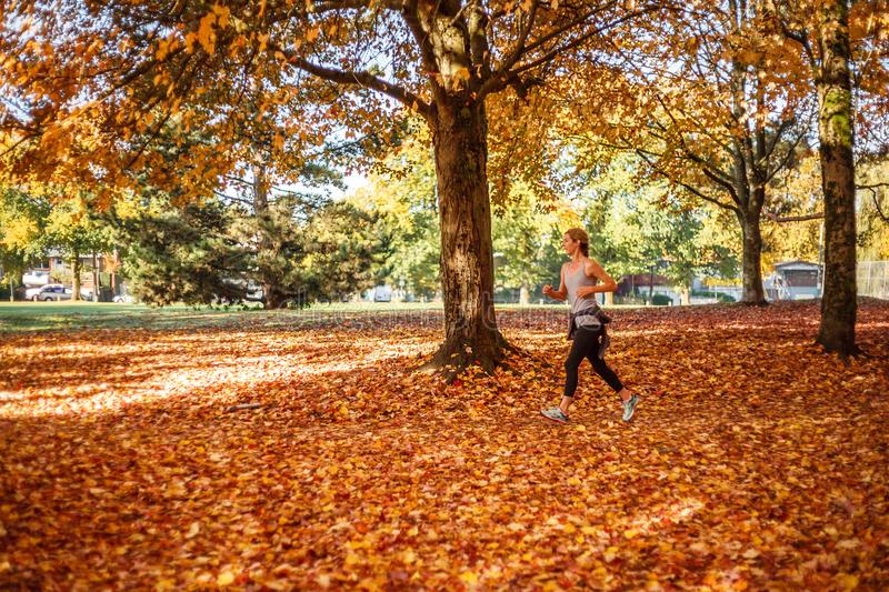 Vancouver Canada - October 29, 2017 Sporty young woman running in the autumn yellow park in the morning. royalty free stock photography