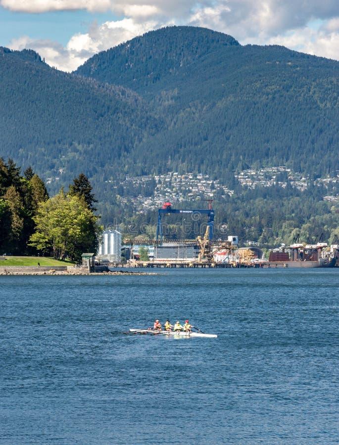 Vancouver, Columbia Brit?nica, - 5 de mayo de 2019: Scull brillantemente vestido que rema al grupo en puerto del carb?n imágenes de archivo libres de regalías