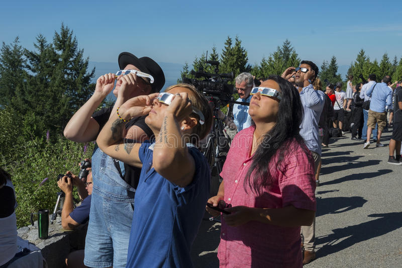 Vancouver eclipse of the sun. People using special glasses to view the 2017 eclipse of the sun on Cypress Mountain lookout near Vancouver Canada stock photography