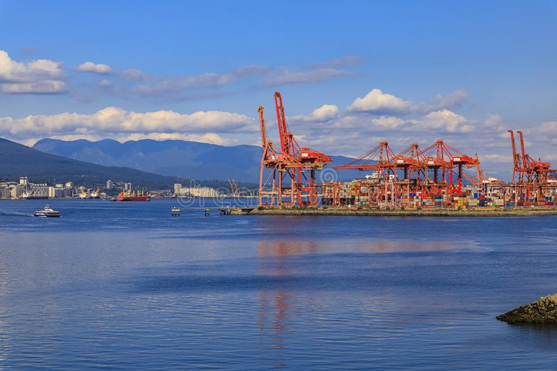 Vancouver harbour with red gantry cranes and cargo shipping containers at the Centerm terminal on the waterfront, Canada royalty free stock photos