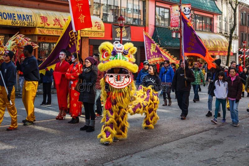 VANCOUVER KANADA - Februari 18, 2014: Folket i gula Lion Costume på det kinesiska nya året ståtar i den Vancouver kineskvarteret royaltyfria bilder