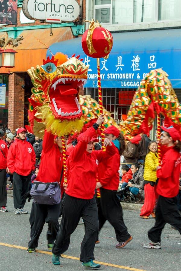 VANCOUVER KANADA - Februari 2, 2014: Folket som spelar draken, dansar för kinesiskt nytt år i kineskvarter arkivfoto