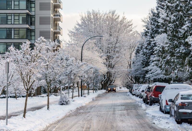 VANCOUVER KANADA - Februari 13, 2019: stads- gata med bilar och träd i snö royaltyfri bild