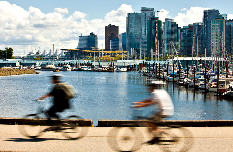 Two cyclists pedaling. Along the seawall in Stanley Park with Vancouver harbour in the background stock images