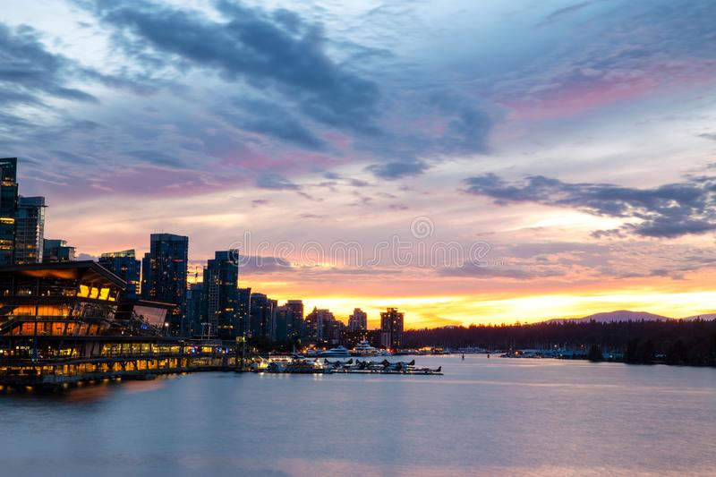 Vancouver Skyline and Cityscape at Sunset in Summer. An incredible Sunset illuminates the Summer sky over Vancouver, BC silhouetting the cityscape as the lights royalty free stock photography