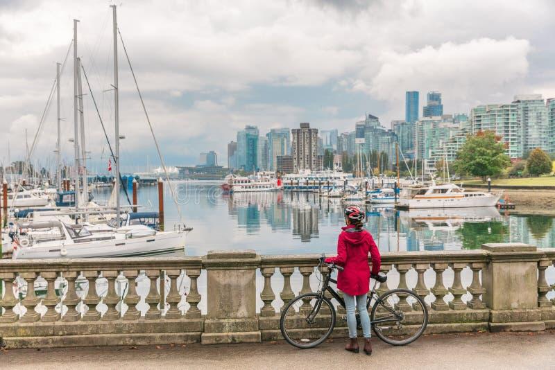 Vancouver som cyklar kvinnacyklisten som gör uthyrnings- aktivitet för aktiv sportlivsstilcykel i Stanley, parkerar på kolhamnen, fotografering för bildbyråer