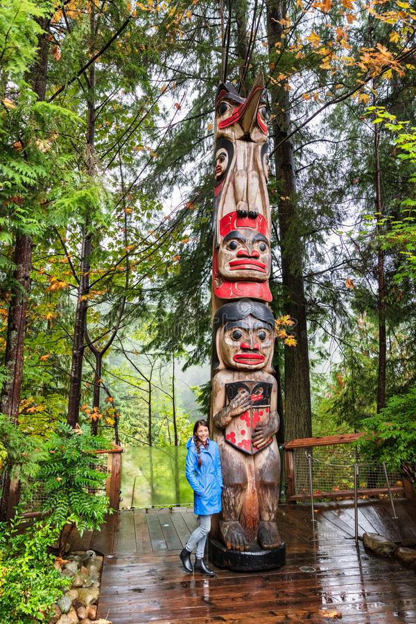 Vancouver tourist woman posing by totem pole, British Columbia, Canada. Asian girl visiting famous popular tourism attraction in stock image