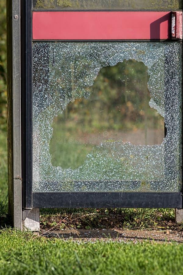 Vandalism med slagit exponeringsglas på den brittiska telefonasken Anti--soci royaltyfri foto
