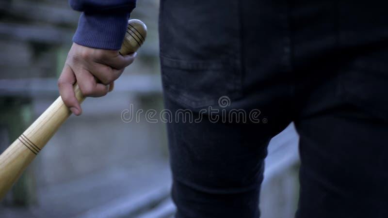 Vandalism, young man walking on stadium tribune with baseball bat, youth gang. Stock photo royalty free stock images