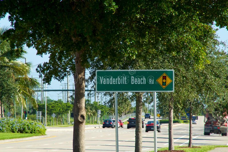 Vanderbilt Beach road sign with traffic. A green Vanderbilt Beach Rd sign on Livingston Road in Naples florida with morning traffic stock images