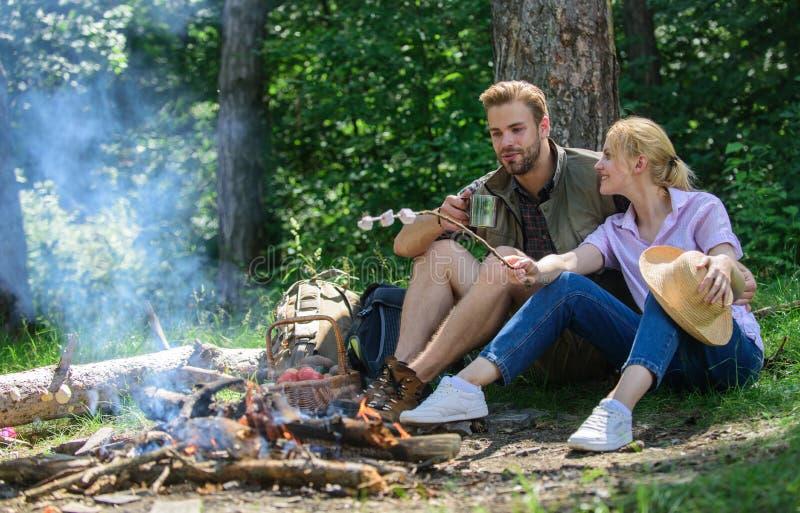 Vandringpicknick Partagandeavbrott som äter naturbakgrund Förälskad campa skogvandring för par Par sitter nära brasa äter fotografering för bildbyråer