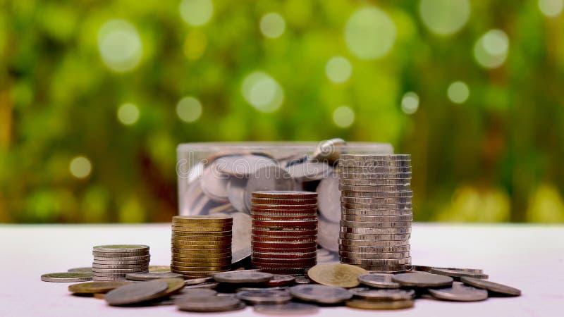 Vang en zet muntstukken in een spaarvarken op een natuurlijke achtergrond royalty-vrije stock afbeelding